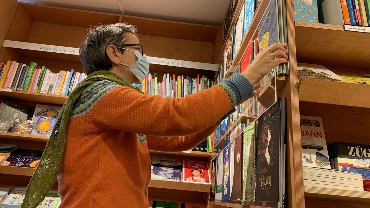 Dame mit kurzen Haaren und Maske sortiert Bücher in ein Regal ein