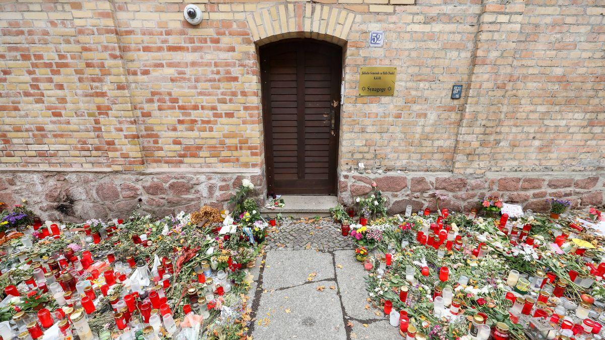 18.10.2019, Sachsen-Anhalt, Halle: Nur noch ein schmaler Weg führt zwischen den Blumen und Kerzen zur Tür der Synagoge Halle.