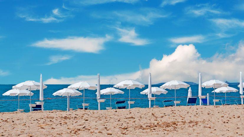 Weiße Sonnenschirme an einem Strand (Symbolbild)