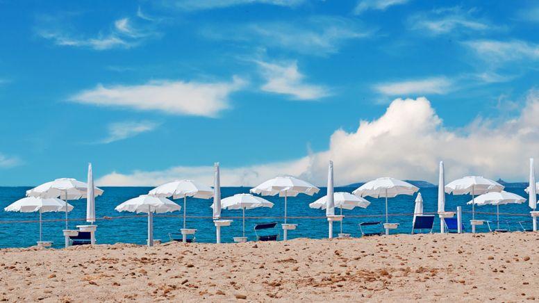 Weiße Sonnenschirme an einem Strand (Symbolbild) | Bild:stock.adobe.com/Gabriele Maltinti