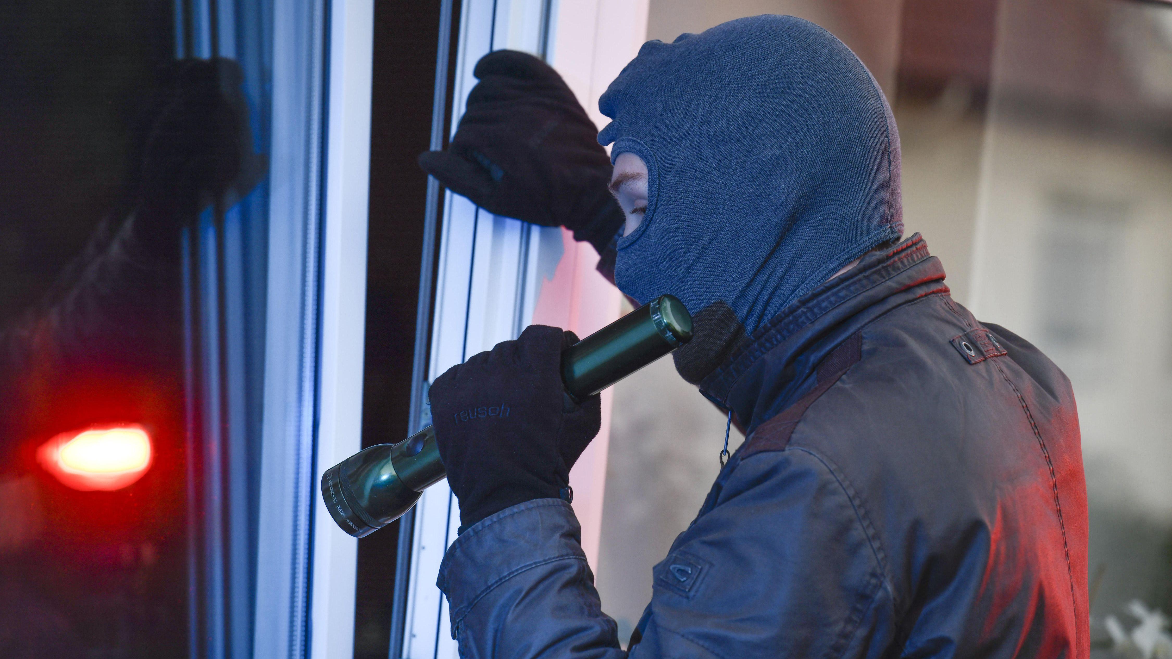 Ein maskierter Mann steht mit einer Taschenlampe vor einem Fenster