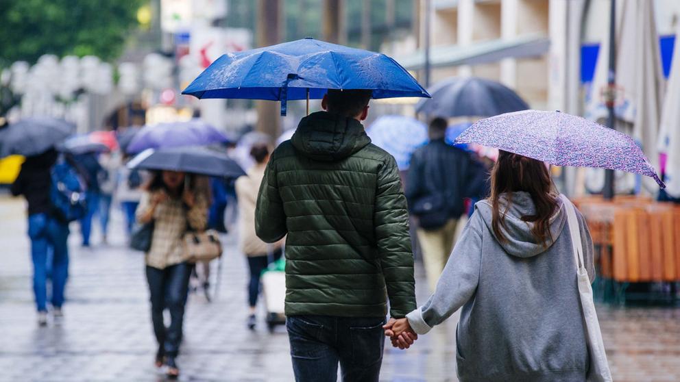 in Paar mit Regenschirmen in der Münchner Fußgängerzone. | Bild:Johanna Schlüter/BR