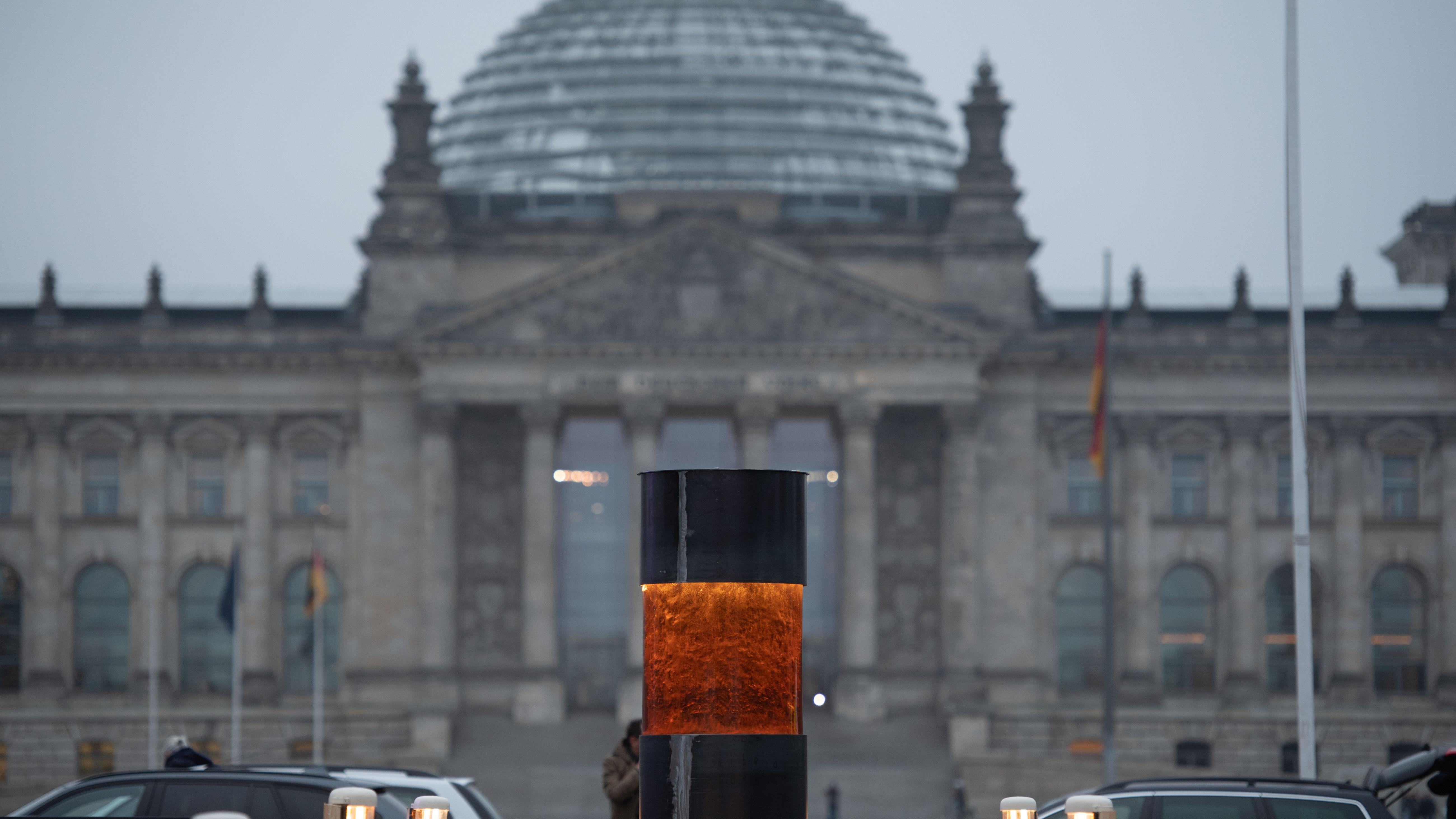 Die Säule, in das Asche von Auschwitzopfern eingegossen worden sein soll, klein im Vordergrund. Dahinter der Reichstag mit seiner Kuppel. nd eine Klage.