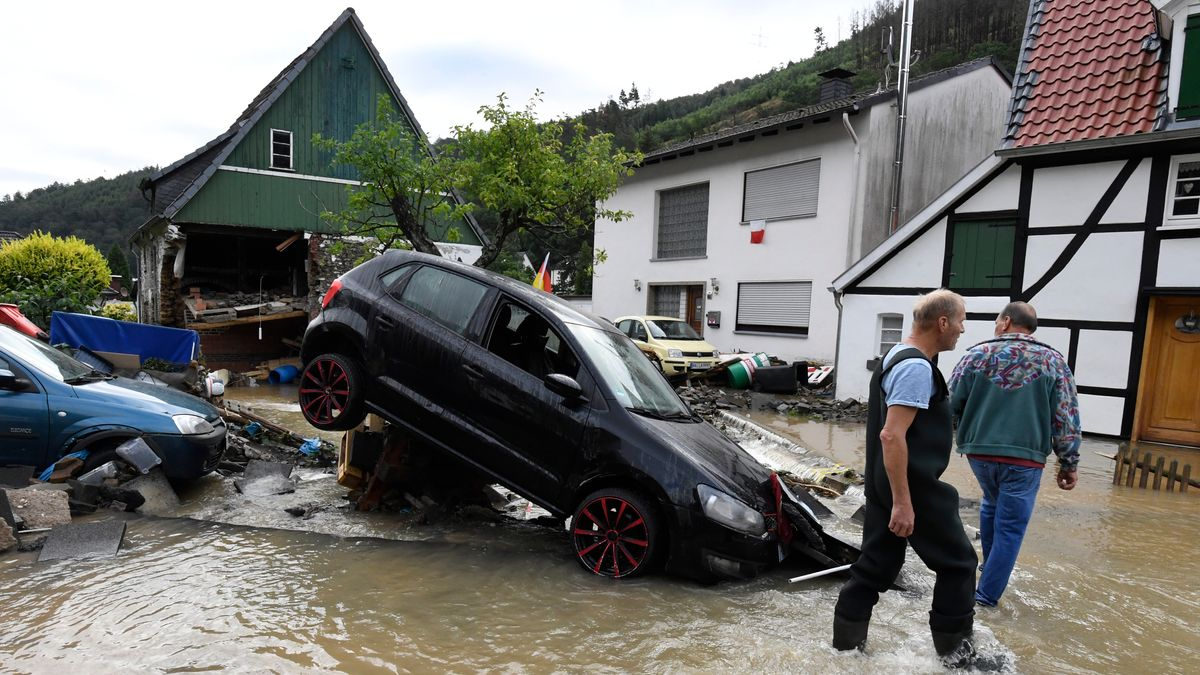 Anwohner schauen sich die Schäden an, die die Überflutung des Nahmerbach am Vorabend mit sich gebracht hatte.