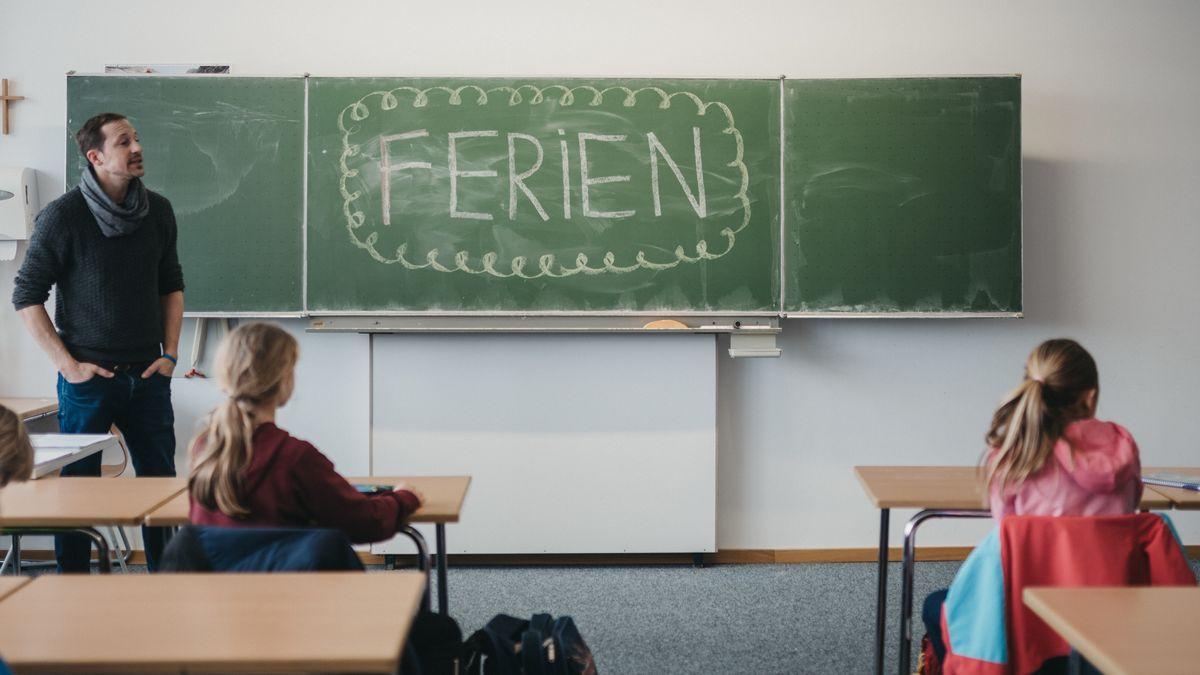 Schüler sitzen vor einer Tafel auf der Ferien steht