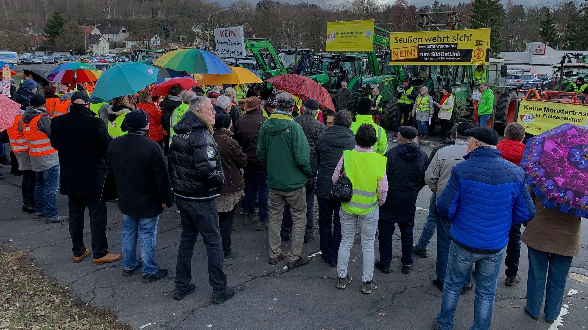 Eine Gruppe demonstrierender Menschen stehen vor Traktoren mit Bannern gegen den Südostlink.