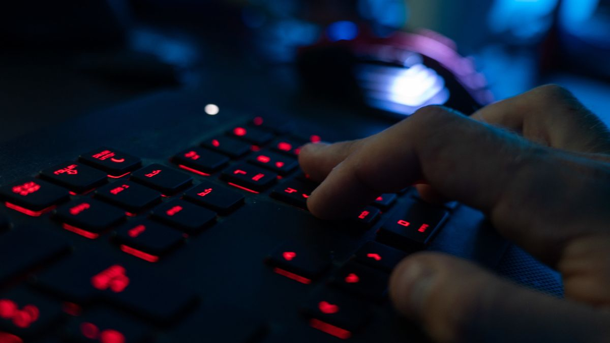 Finger tippen auf einer dunkel beleuchteten Tastatur.