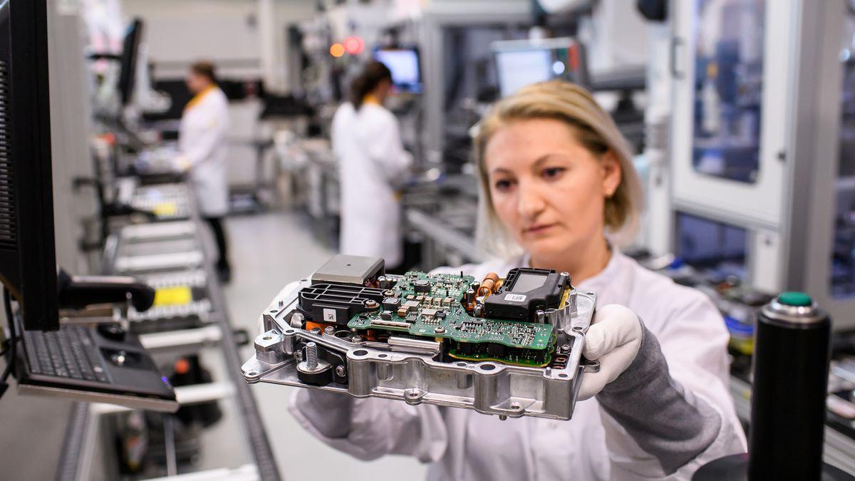 Eine Frau im weißen Kittel hält ein elektronisches Bauteil in den Händen.