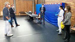 Hofs Landrat Oliver Bär steht mit Hausärzten in einer umfunktionierten Turnhalle. | Bild:Landratsamt Hof