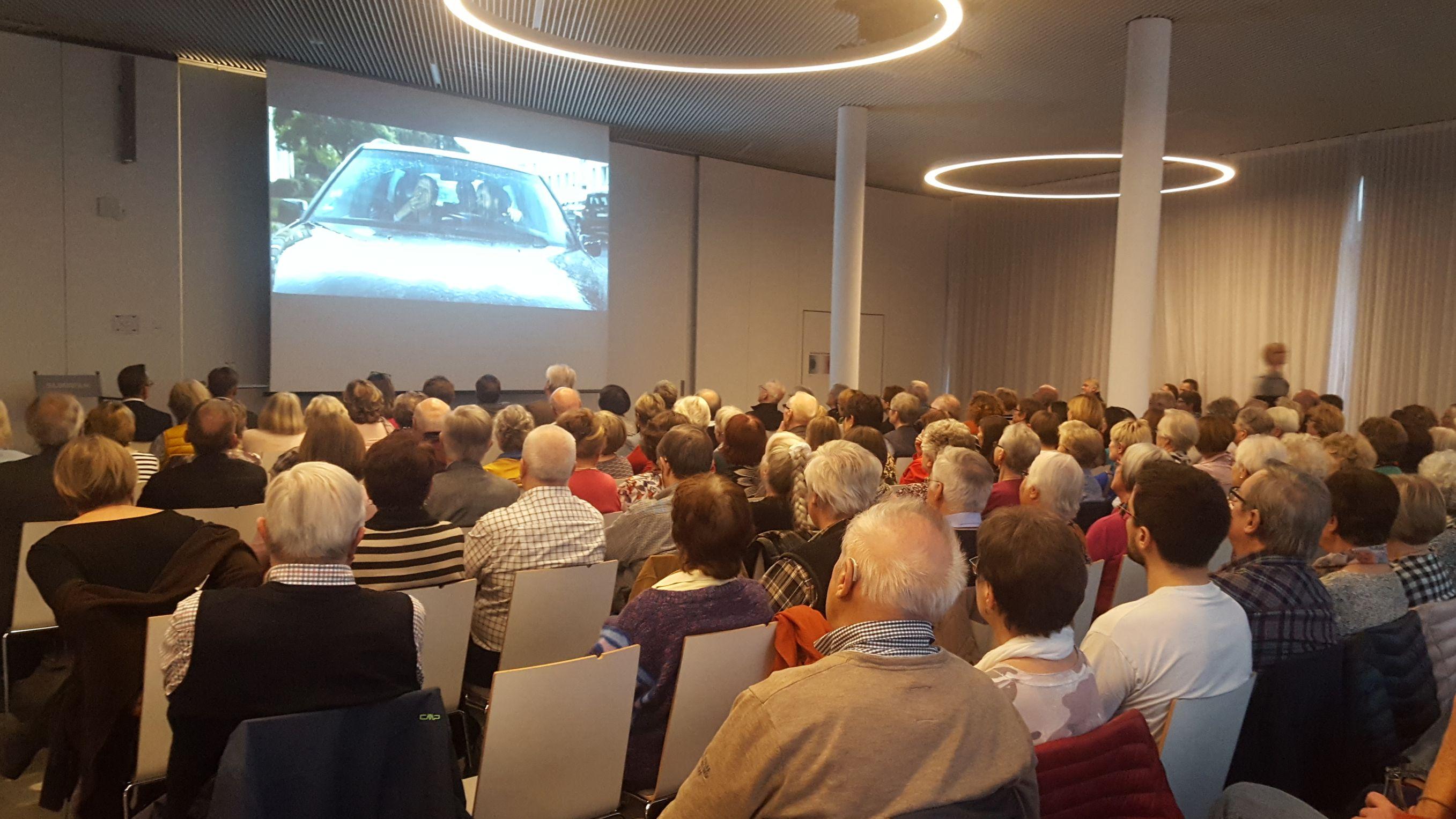 Senioren schauen mit ihren Angehörigen einen Film auf einer Leinwand.