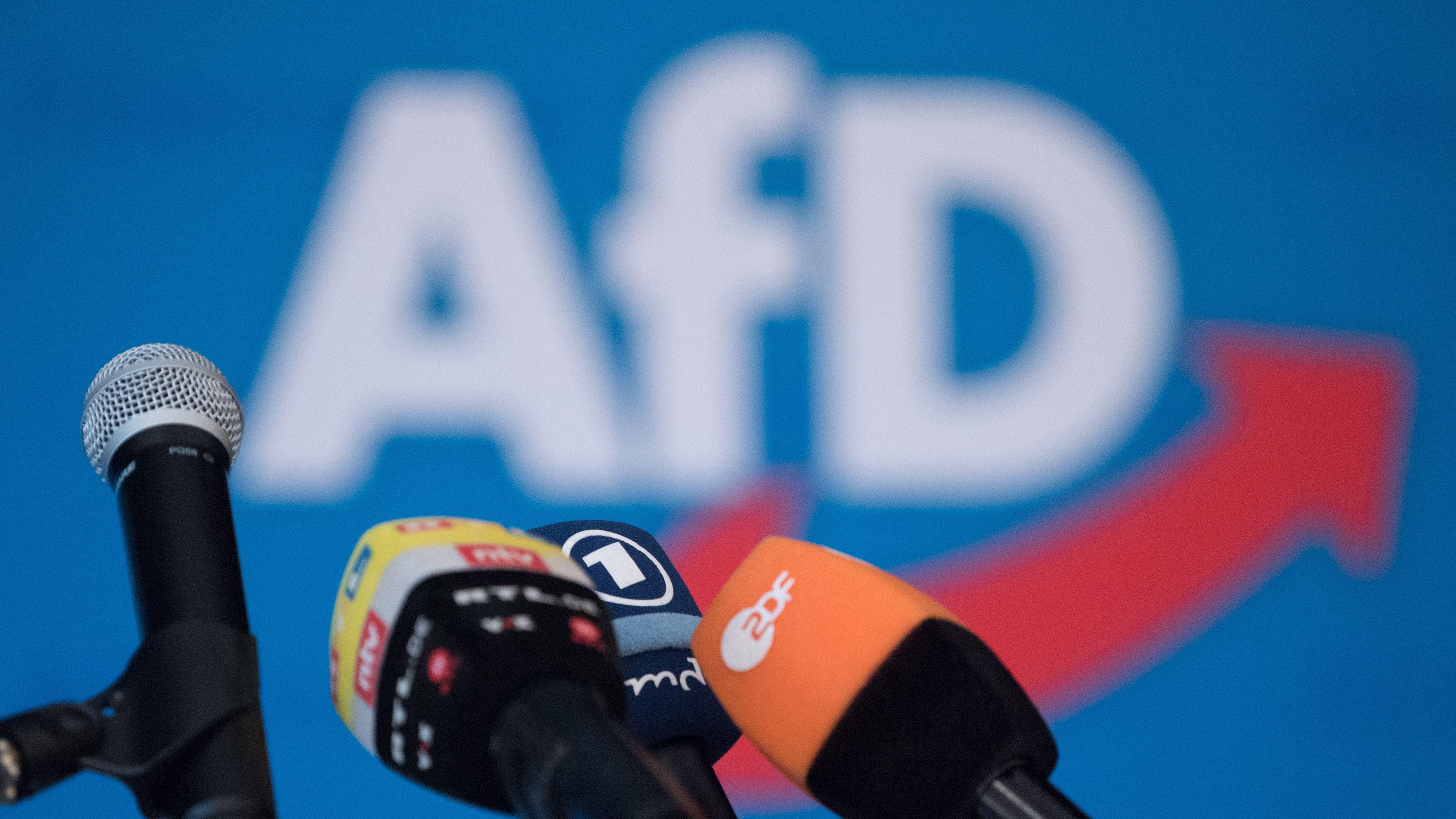Verschiedene Mikrofone vor AfD-Banner.