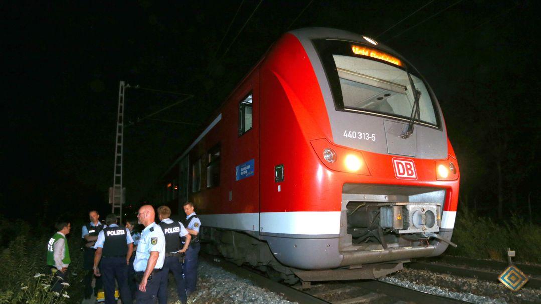 Polizisten stehen in Würzburg neben einem Regionalzug, in dem ein 17-jähriger Afghane mit Axt und Messer Passagiere attackiert hat.