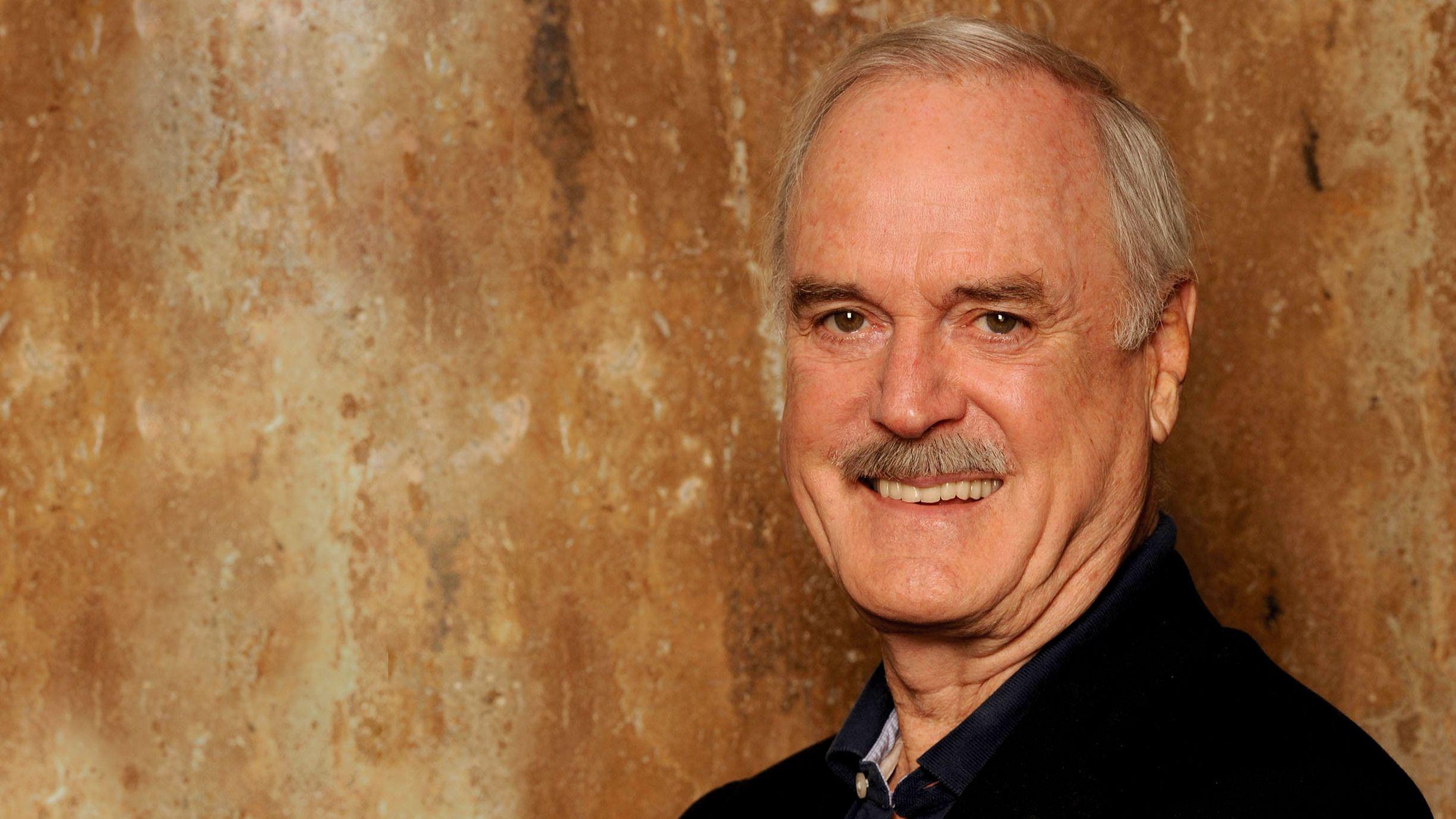 John Cleese steht vor einer ockerfarbenen Wand und lächelt in die Kamera