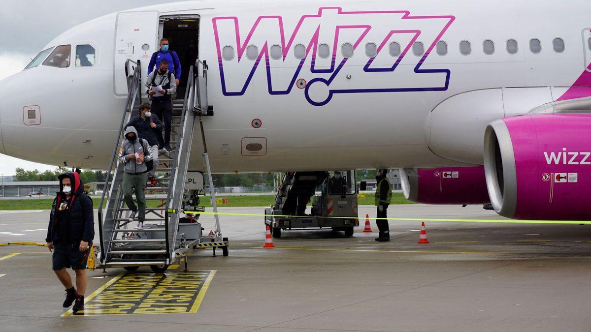 Passagiere mit Mund- und Nasenschutz steigen am Allgäu Airport aus einer Wizz Air Maschine aus