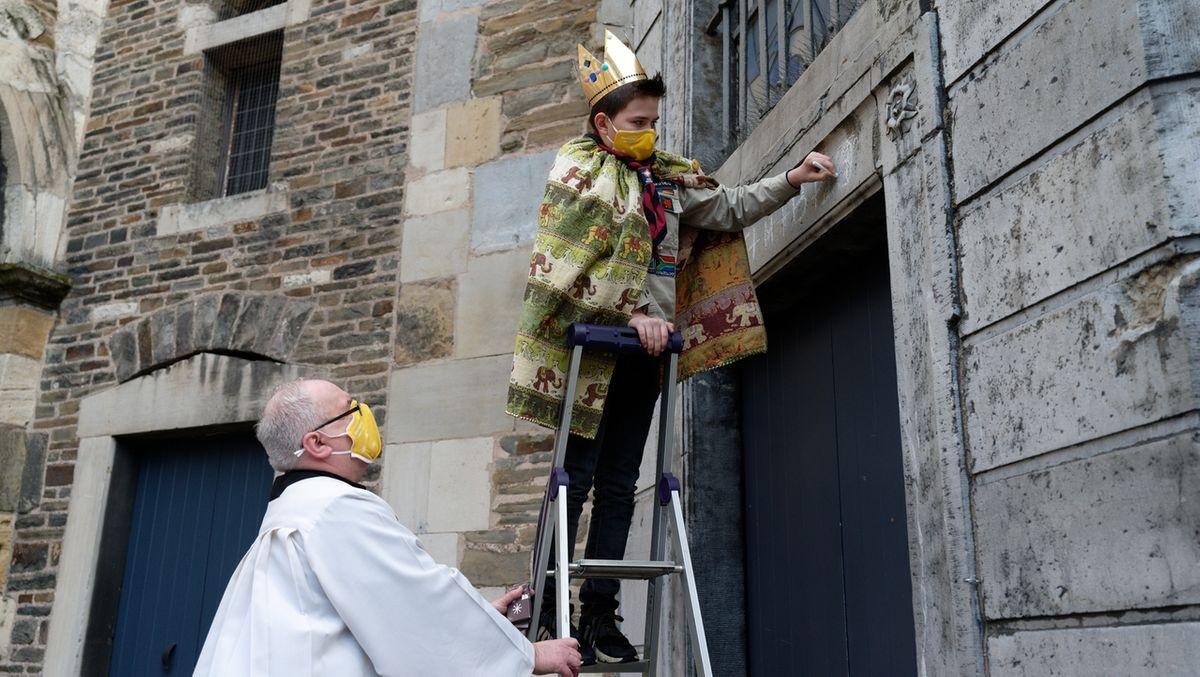 Ein Sternsinger mit Mundschutz steht auf einer Leiter und segnet ein Haus.