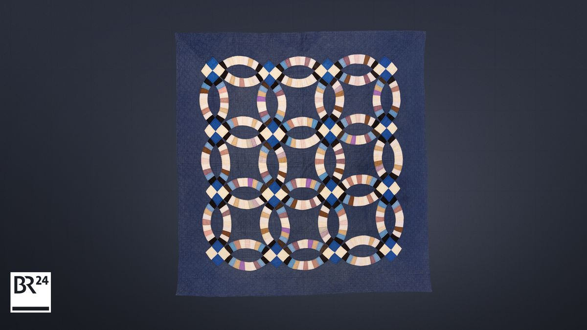 Eine blaugrundige Decke mit 9 in sich verschlungenen Ringen