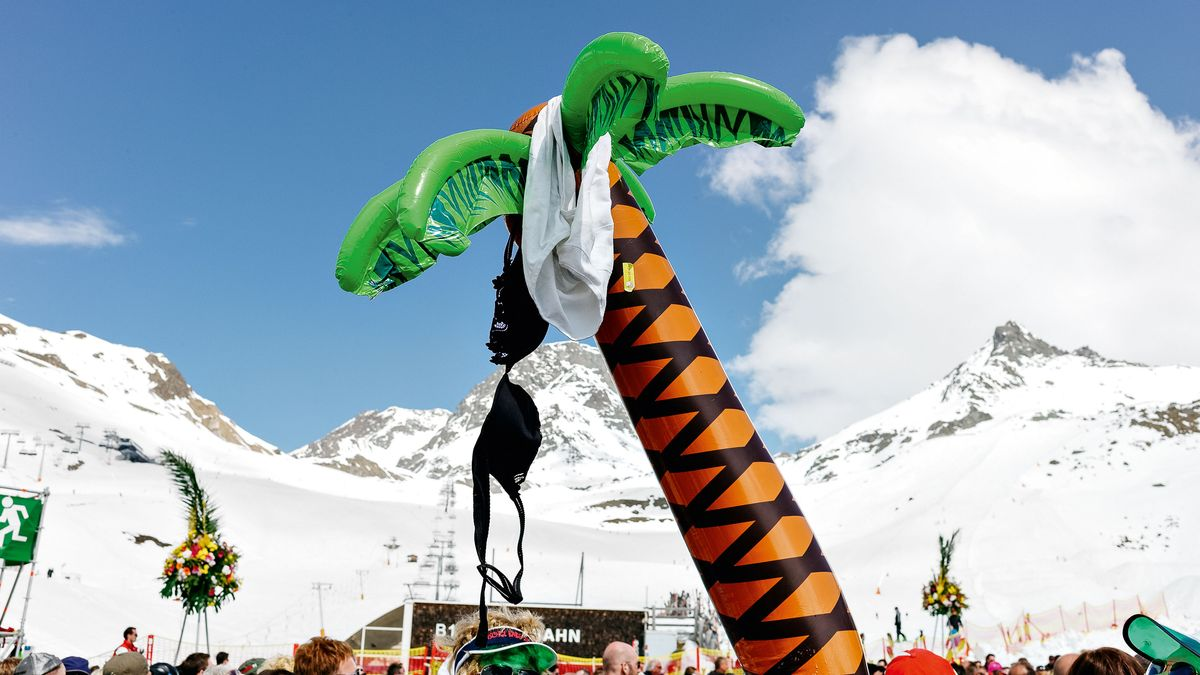 Aufblasbare Gummipalme, an der ein schwarzer BH und eine weiße Feinrippunterhose hängen, vor verschneiter Alpenkulisse. Im Hintergrund eine Menschenmenge und ein Skilift.