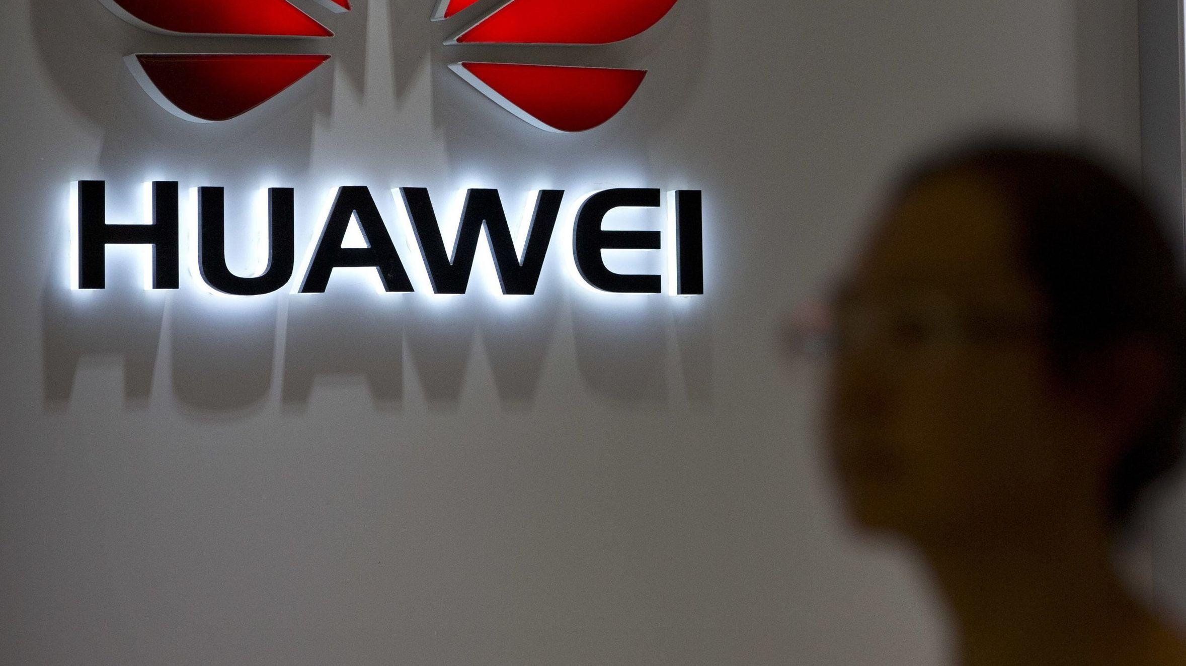 Frau (unscharf) vor Huawei-Logo (angeschnitten)