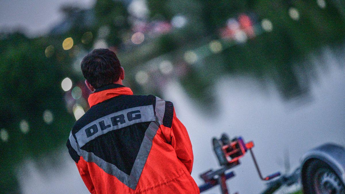 Ein Mitarbeiter der Deutschen Lebens-Rettungs-Gesellschaft (DLRG) steht am Ufer eines Sees.