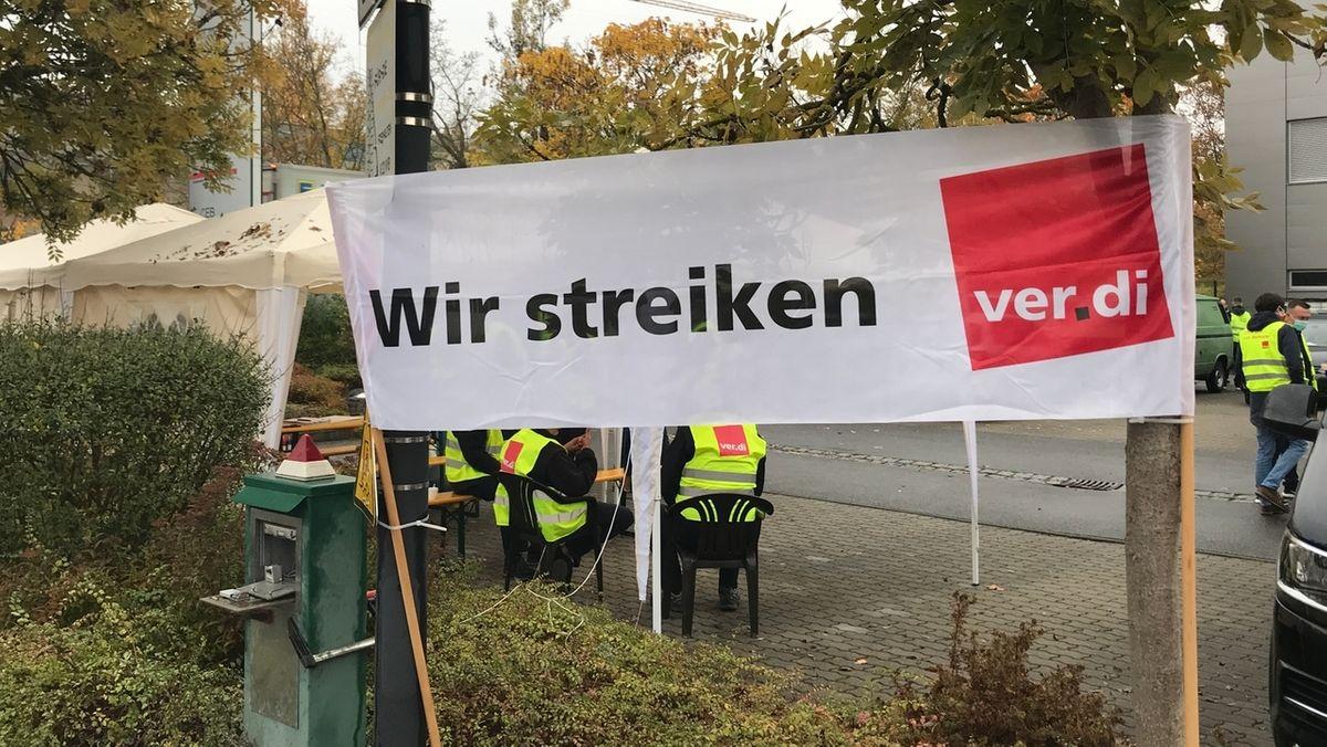 """Streikende in gelben Westen sitzen an einer straße, dazu ein Banner mit der Aufschrift """"Wir streiken, Verdi""""."""