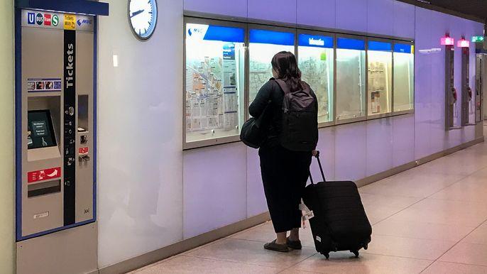 Eine Frau steht im Sperrengeschoss des Münchner Hauptbahnhofs und studiert den Fahrplan.