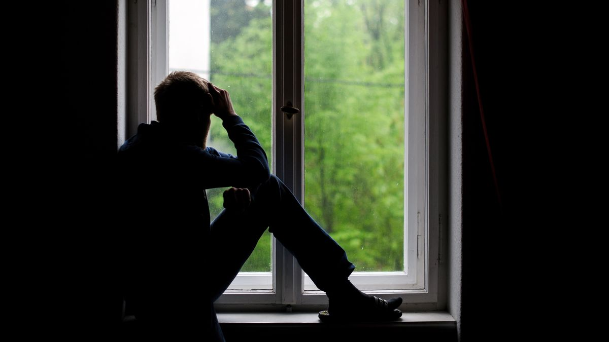 Ein Mann sitzt auf einem Fensterbrett.