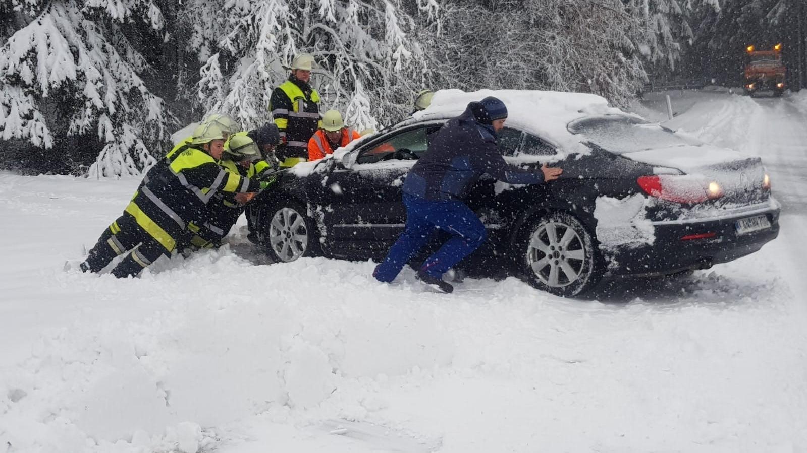 Feuerwehrkräfte schieben Auto auf die Straße zurück