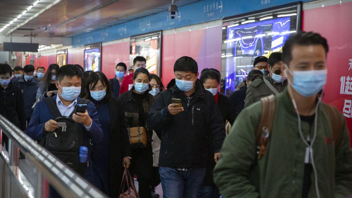Pendler schauen auf ihre Smartphones, während sie durch eine U-Bahn-Station in Peking gehen.