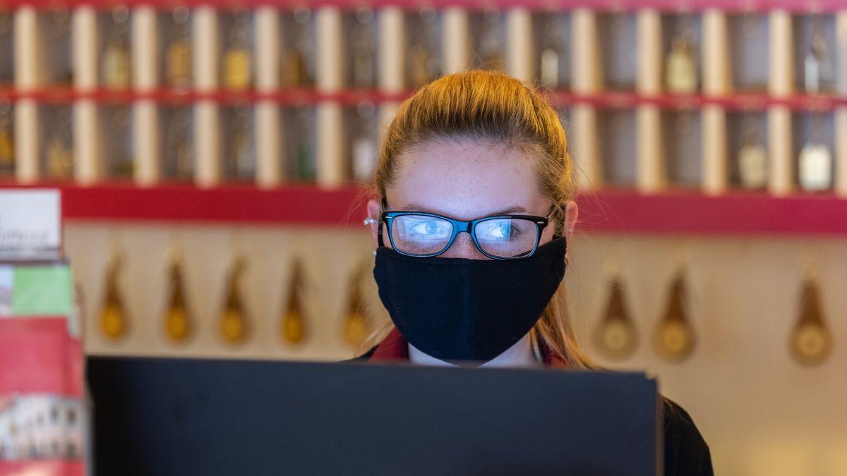 Eine Frau steht in einem Hotel mit Mundschutz an der Rezeption