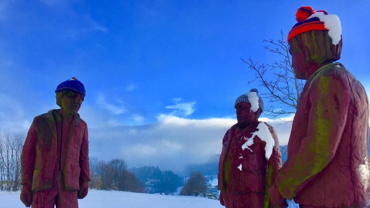 Überlebensgroße Holzfiguren am Ortseingang von Bodenmais. Im Winter mit Strickmützen auf den Köpfen.