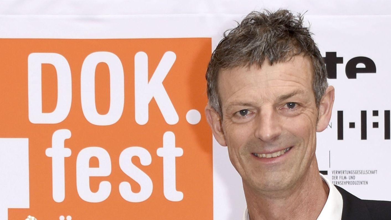 DOKfest-Leiter Daniel Sponsel steht vor einer Wand Sponsorennamen und dem Festivallogo