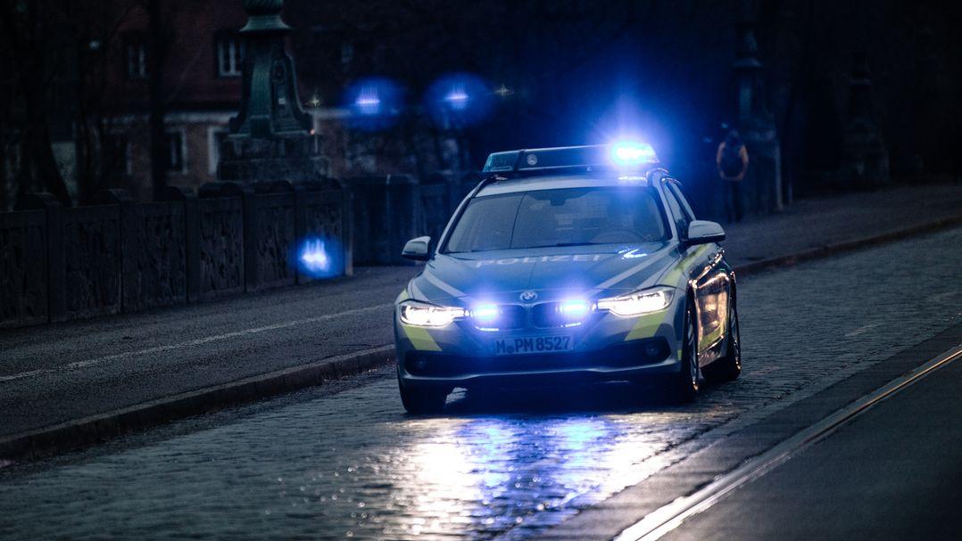 Ein Polizeiwagen fährt mit Blaulicht (Symbolbild)
