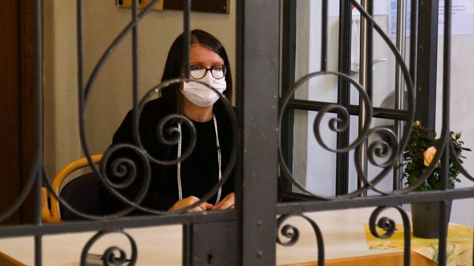Frau hinter einem Gitter in einer Kirche