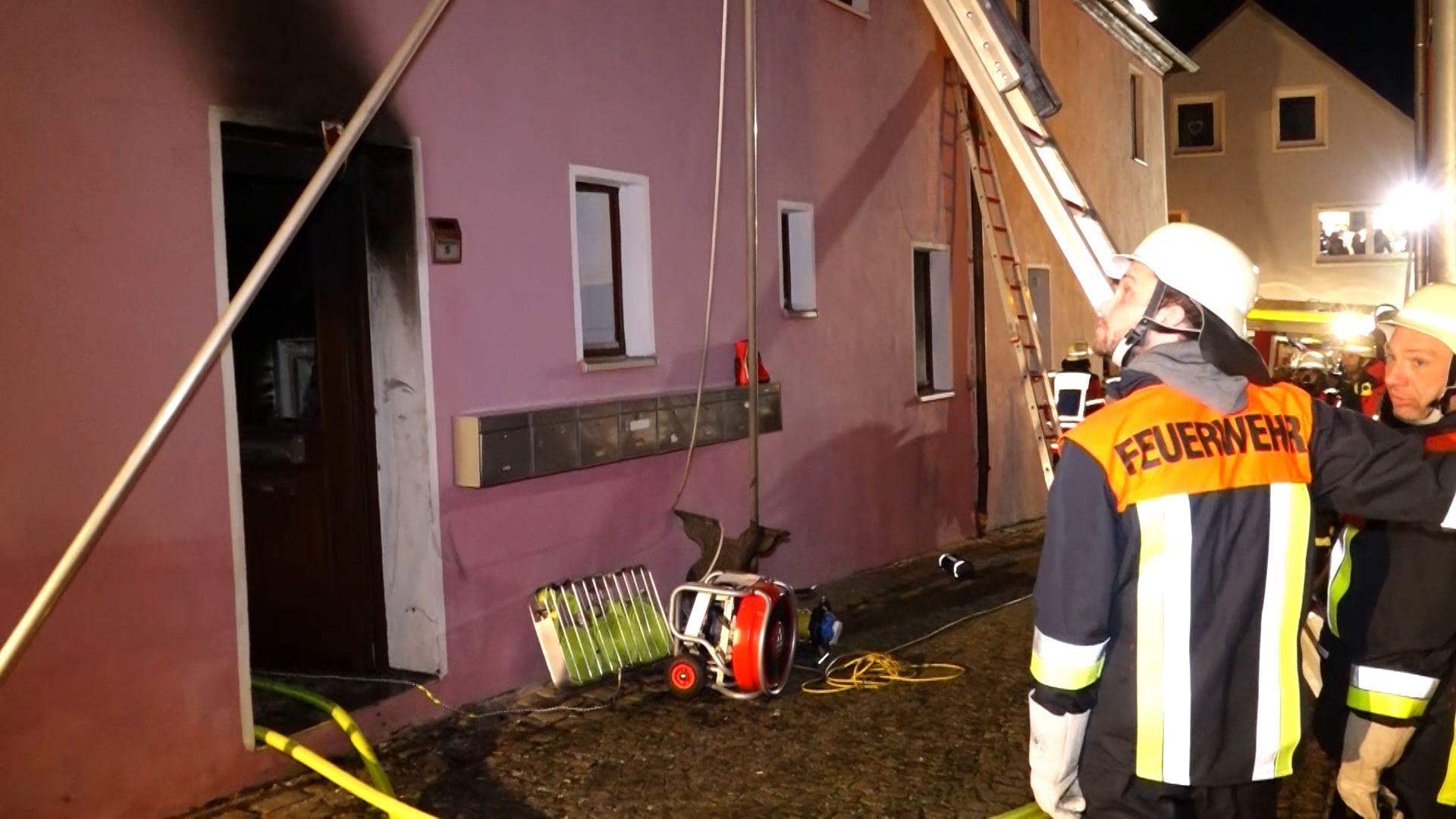 Die Feuerwehr bei Löscharbeiten vor dem Haus.