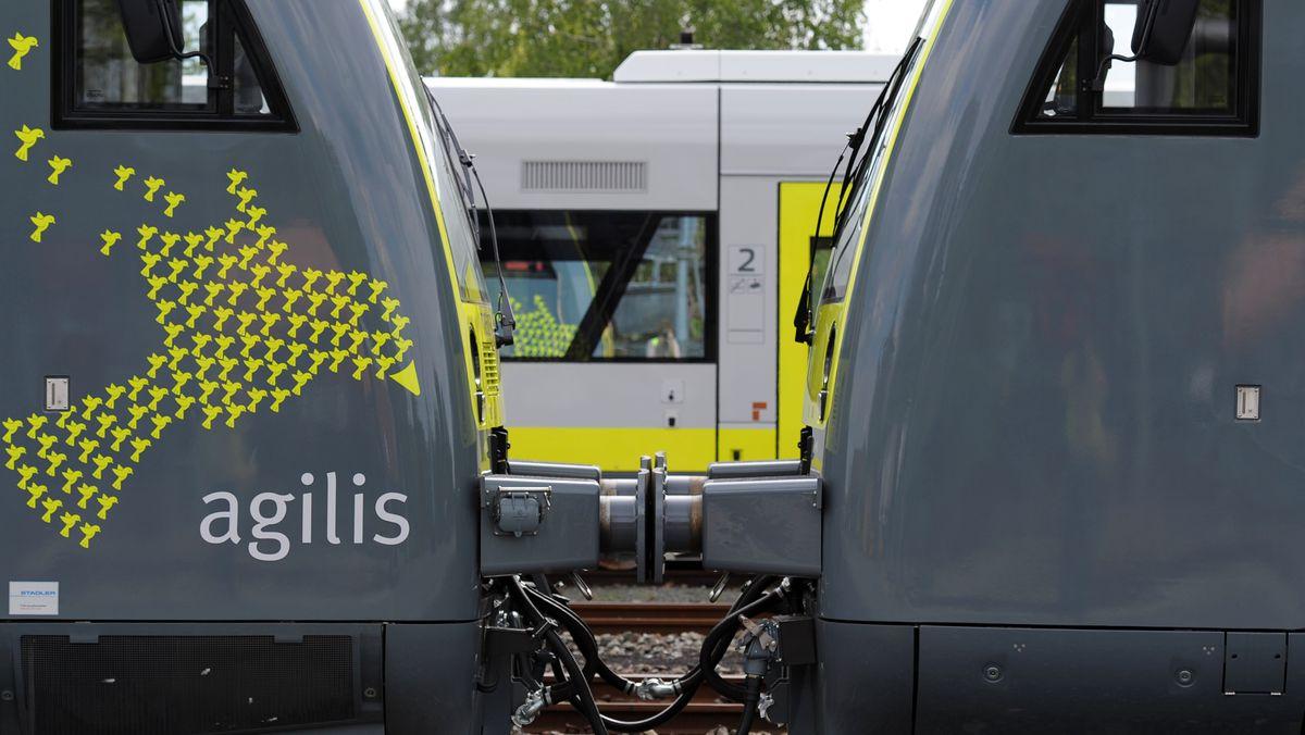 Zwei Triebwagen von Agilis stehen auf einem Nebengleis im Bahnhof.