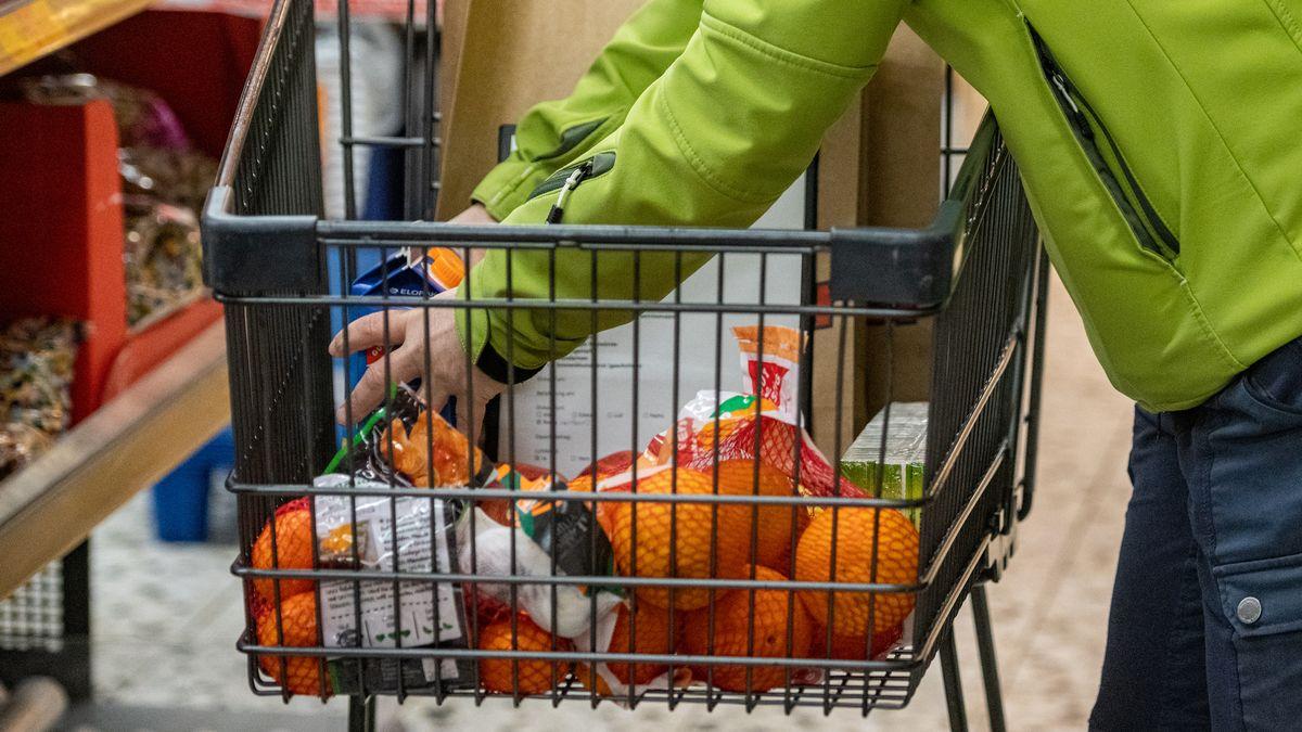 Eine Frau legt in einem Supermarkt Lebensmittel in einen Einkaufswagen. Die Helferin besorgt für Senioren und Kranke Lebensmittel.