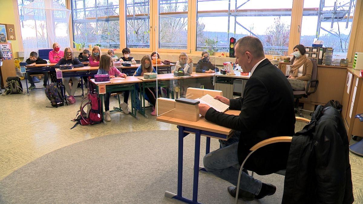 Bürgermeister Frank Stumpf (FWD) liest hinter einer Plexiglasscheibe den Schülern der Grundschule Naila etwas vor, die mit Masken an den Schulbänken sitzen.