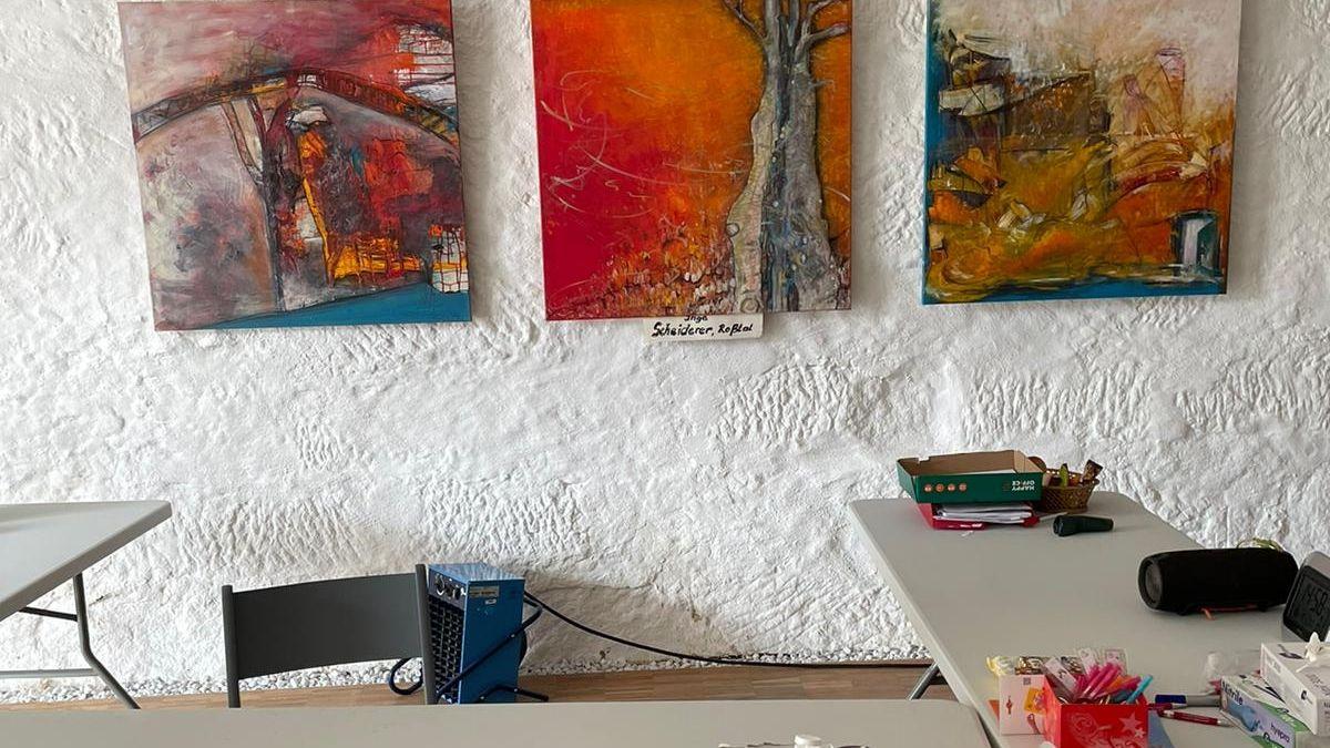 Drei Bilder hängen hinter einem Tisch mit Büromaterial.