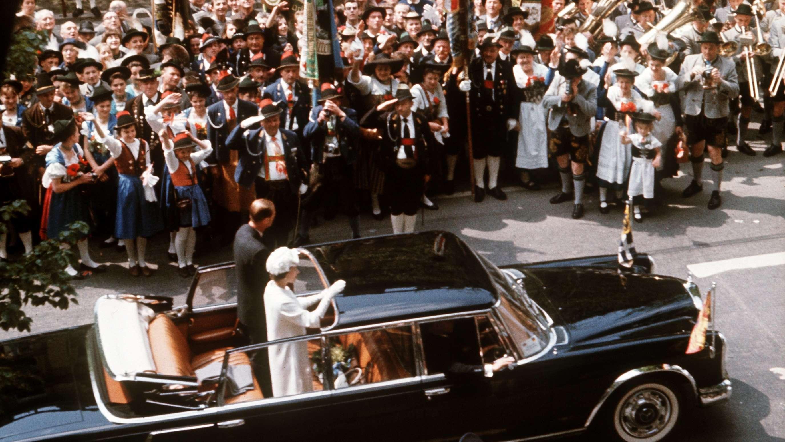 München-Besuch von Queen Elizabeth II. und Ehemann Prinz Philip 1965: Trachtengruppen jubeln dem Königspaar zu.