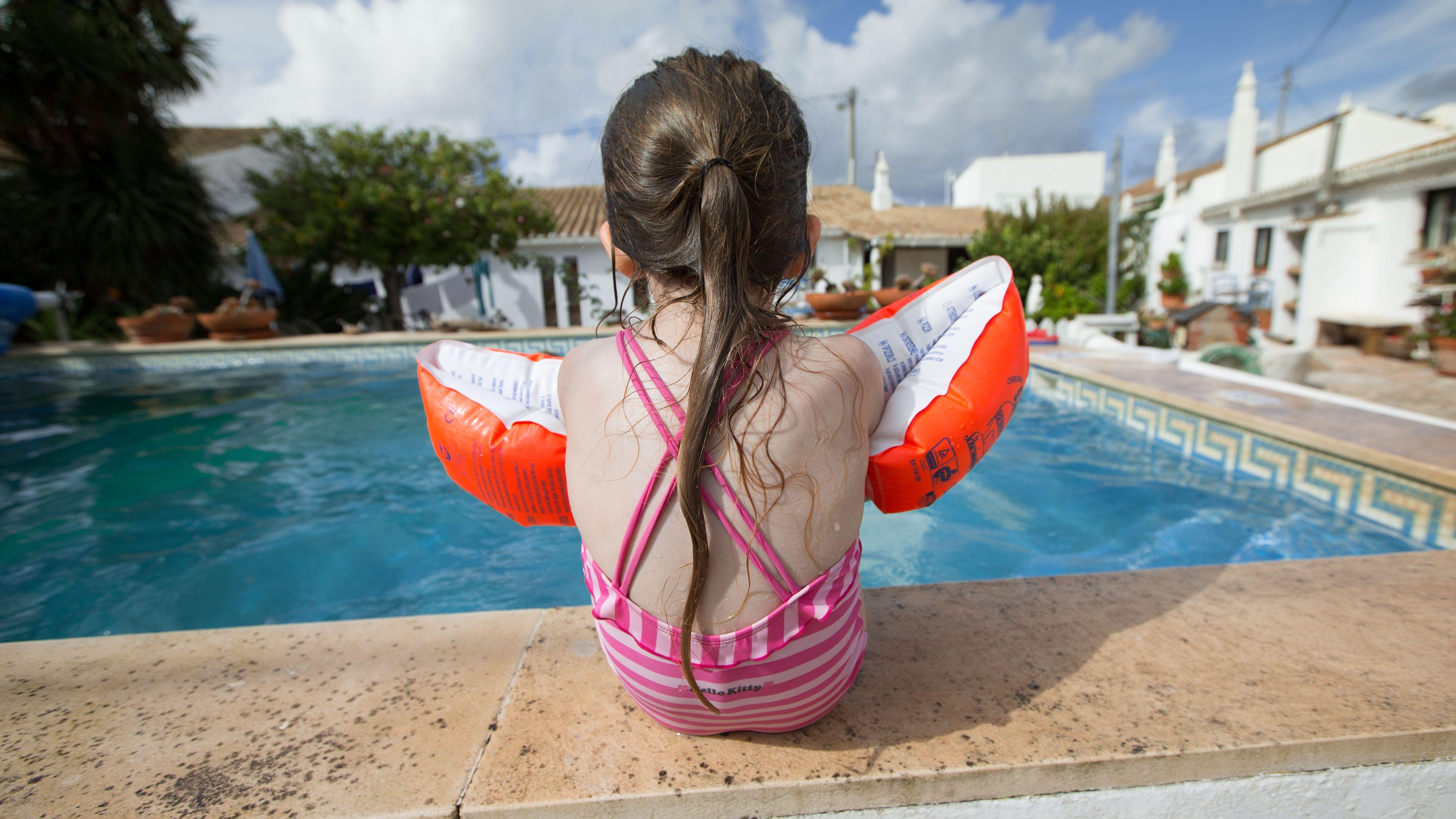 Kind mit Schwimmflügeln am Schwimmbeckenrand