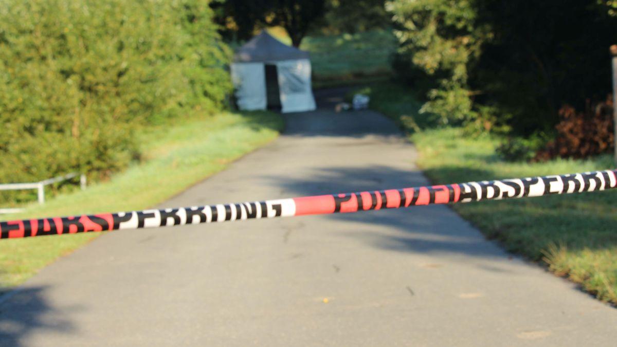 Ein rot-weißes Absperrband hängt vor einem Radweg.