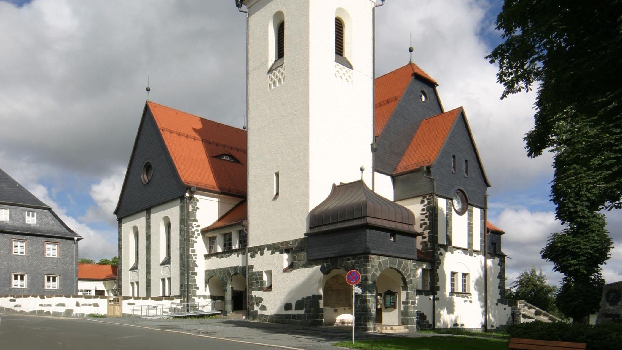 Kirche aus dem Jahr 1908 mit weißen Mauern, Schiefergiebeln und roten Dächern