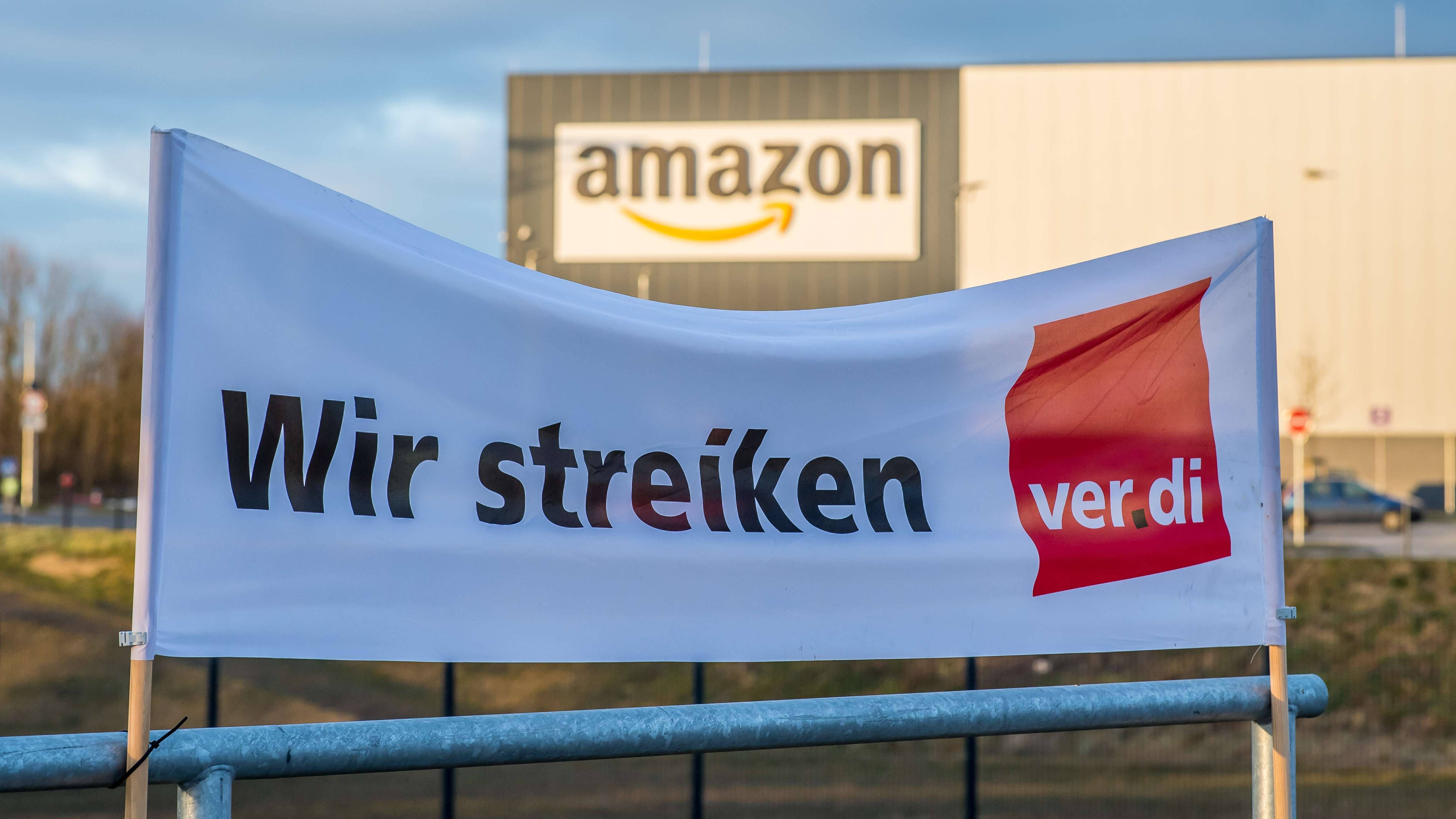 """Symbolbild: Ein Verdi Banner mit der Aufschrift: """"Wir streiken"""" im März 2018 vor dem Amazon-Logistik-Zentrum in Werne,  , Nordrhein-Westfalen."""