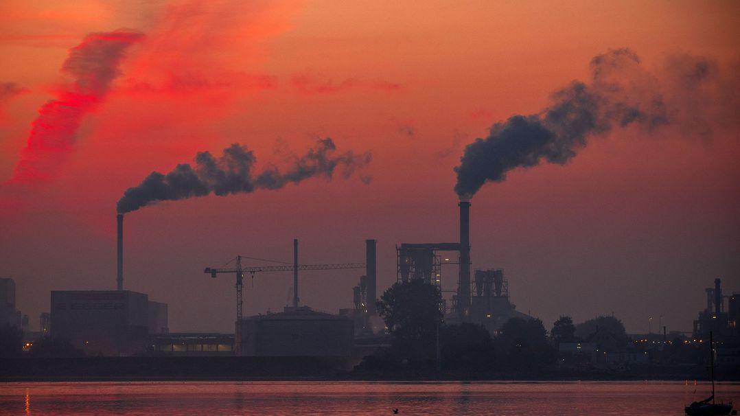 Aus Schornsteinen neben einer Wasserfläche steigt im Morgenrot Rauch auf.