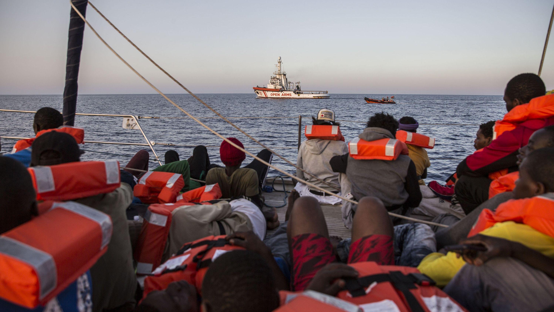 Migranten sitzen auf einem Boot der Hilfsorganisation Mediterranea Saving Humans, während sie vor der Küste der italienischen Insel Lampedusa segeln.