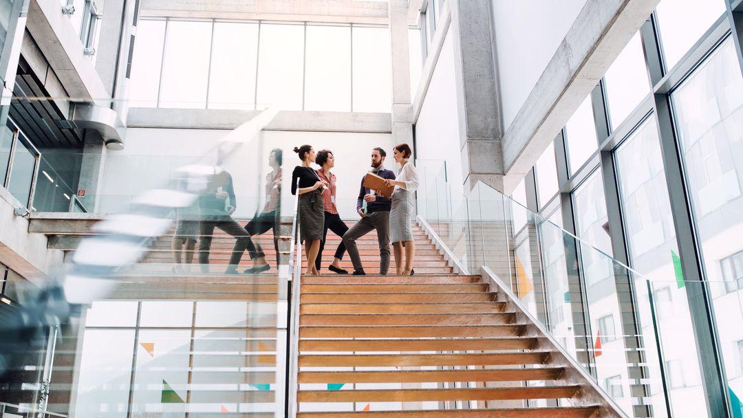 Eine Gruppe junger Mitarbeiter steht auf einer Treppe und unterhält sich.