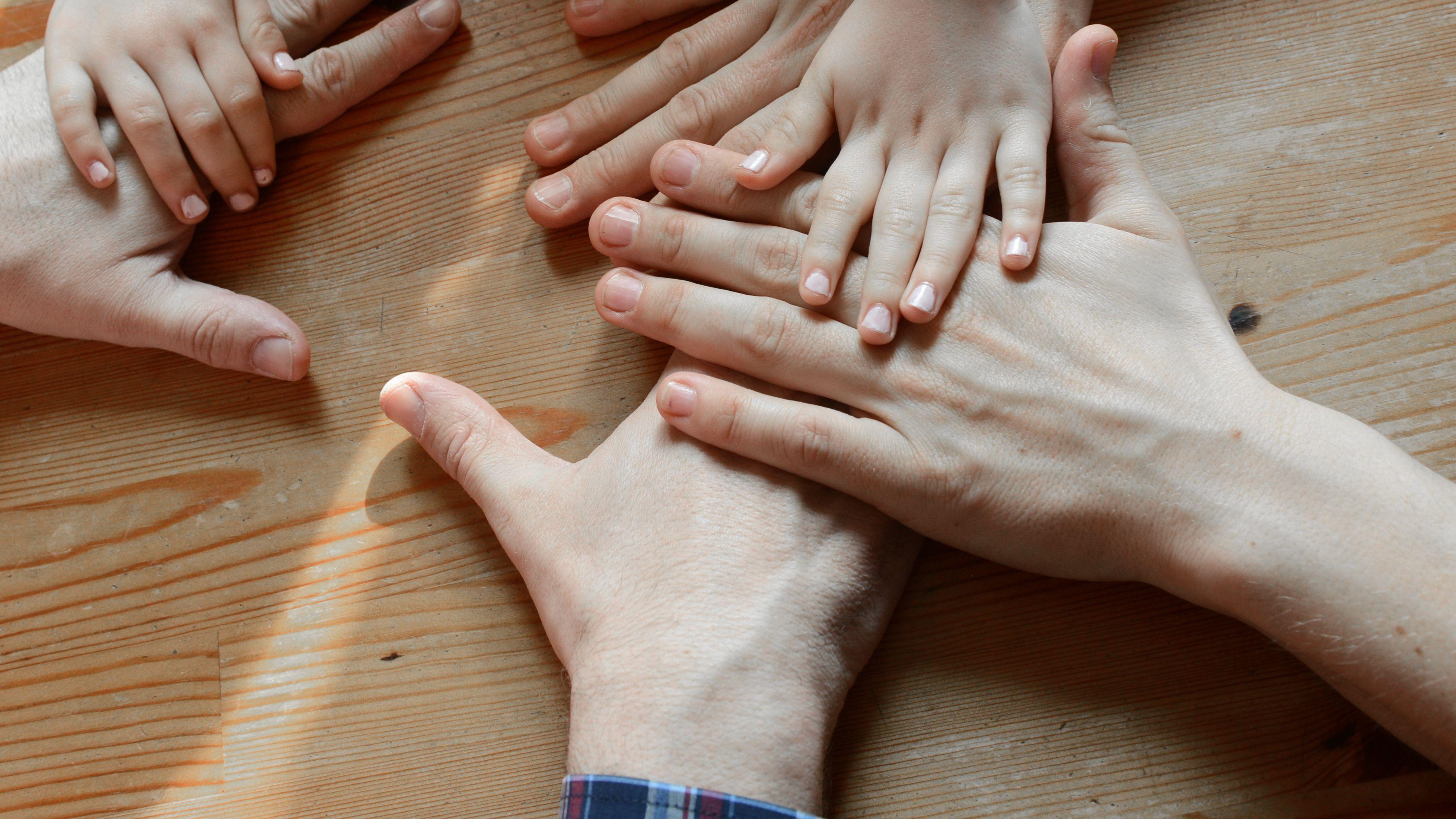 Die Hände von zwei Erwachsenen und einem Kind.