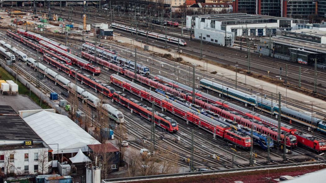 Stehende rote und weiße Züge auf Gleisen am Hirschgarten von oben