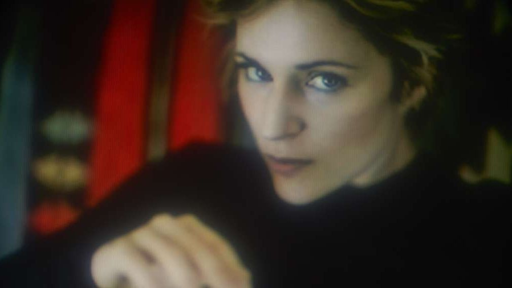 Die Musikerin im schwarzen Pullover blickt leicht schräg in die Kamera.