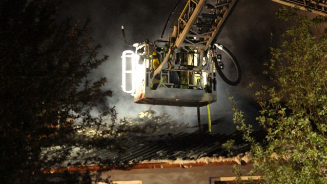 Von einer Feuerwehrkanzel aus löschen Einsatzkräfte das Dach eines Wohnhauses, aus dem dicker Rauch aufsteigt.